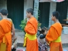 Mönche, die im Rahmen einer täglichen Prozession durch Luang Prabang pilgern